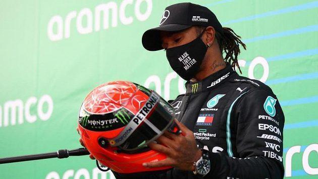 Lewis Hamilton si se zájmem prohlíží Schumacherovu helmu...