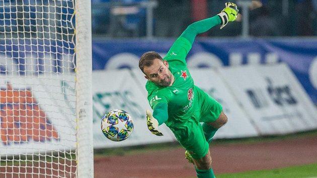 Brankář Slavie Ondřej Kolář se natahuje po míči.