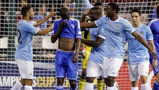 Fotbalista Manchesteru City Micah Richards přijímá gratulace od Gaela Clichyho a Dedrycka Boyaty ke gólu proti Chelsea v St. Louis.