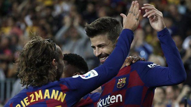 Barcelonští fotbalisté Gerard Pique (vpravo) a Antoine Griezmann oslavují gól proti Valencii.