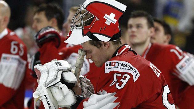 Smutný švýcarský brankář Leonardo Genoni se spoluhráči po finálové porážce se Švédy.