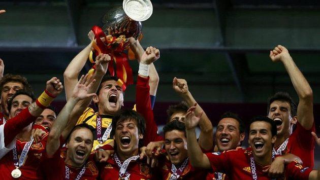 Brankář Španělska Iker Casillas třímá pohár a bouřlivě oslavuje se spoluhráči úspěšnou obhajobu na mistrovství Evropy.