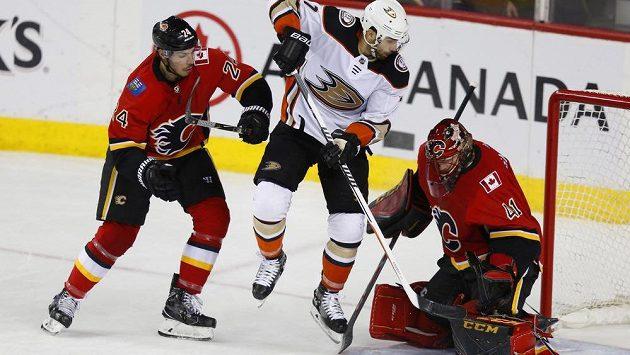 Útočník Anaheimu Andrew Cogliano před brankářem Calgary Mikem Smithem, vlevo zadák Flames Travis Hamonic.