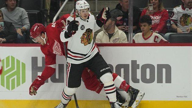 Útočník Chicaga Dominik Kubalík (8) přišpendlil v přípravě před NHL na mantinel obránce Detroitu Wyatta Newpowera.