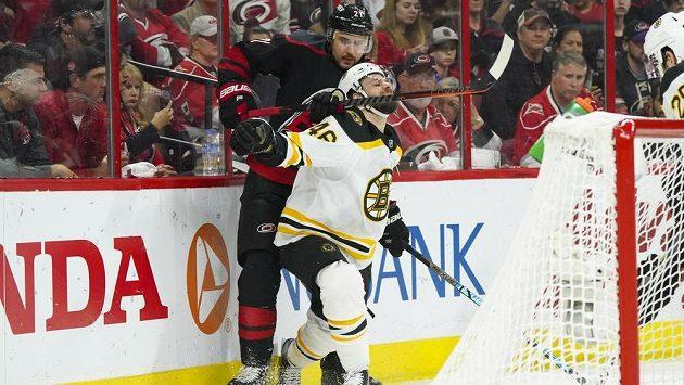 Hokejový útočník Bostonu David Krejčí (46) čelí drsnému ataku Nina Niederreitera z Caroliny Hurricanes v utkání play off NHL.