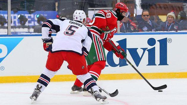 Obránce NY Rangers Dan Girardi (5) dotírá na Jaromíra Jágra z New Jersey Devils v utkání pod širým nebem.