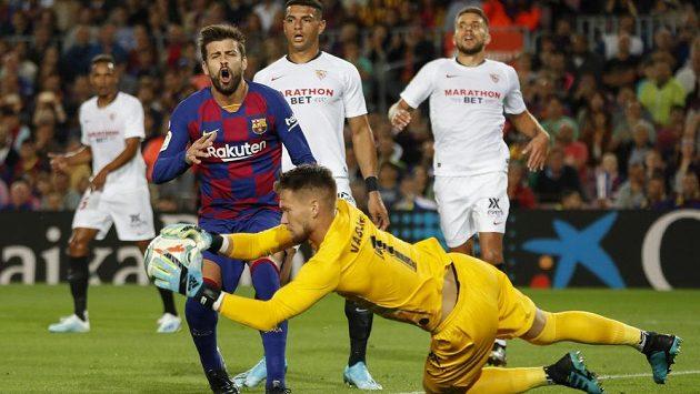 Barcelonský Gerard Pique před brankářem Sevilly Tomášem Vaclíkem.