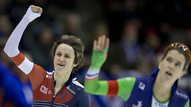 Česká rychlobruslařka Martina Sáblíková se raduje z triumfu na MS na trati 3000 metrů poté, co v poslední jízdě v přímém souboji porazila Ireen Wüstovou (vpravo).