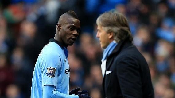 Mario Balotelli (vlevo) se dívá na trenéra Manchesteru City Roberta Manciniho.