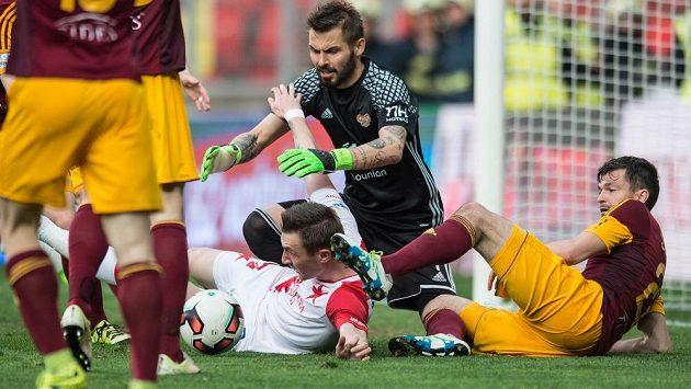 Brankář Dukly Filip Rada se vrhá po míči v duelu se Slavií.