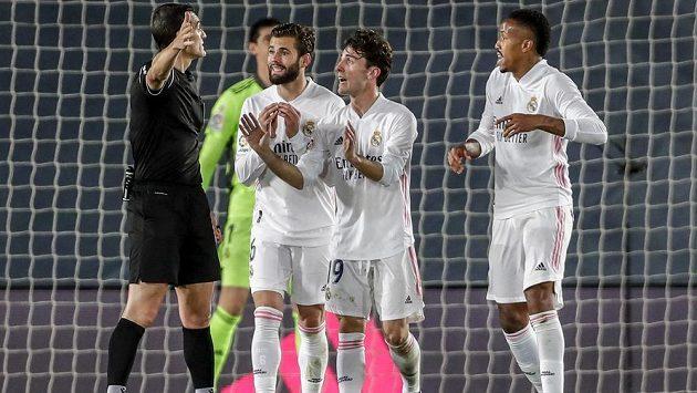 Zklamaní fotbalisté Realu Madrid diskutují s rozhodčím během utkání španělské ligy.