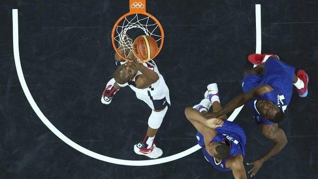 Americký basketbalista Kevin Durant smečuje, bránící Francouzi Boris Diaw (druhý zprava) a Florent Pietrus neměli nárok. Celek USA si připsal na úvod olympijského trunaje vítězství.
