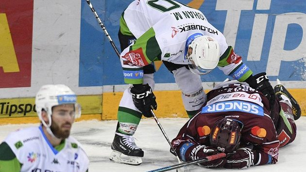 Richard Jarůšek ze Sparty (vpravo) leží na ledě po nárazu do mantinelu. Sklání se nad ním karlovarský Martin Rohan.