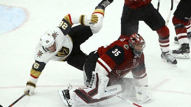 Centr hokejistů Las Vegas Paul Stastny přepadává přes brankáře Arizony Darcyho Kuempera v zápase severoamerické NHL.