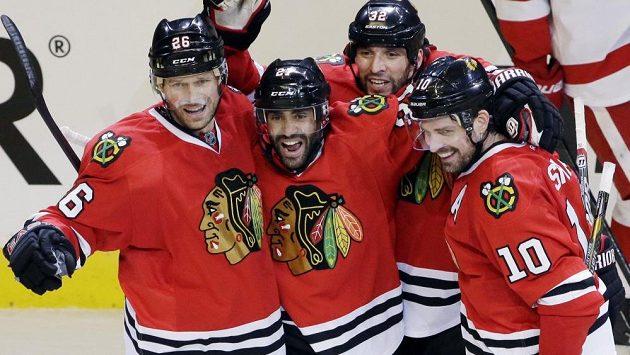 Hokejisté Chicaga (zleva) Michal Handzuš, Johnny Oduya, Michal Rozsíval a Patrick Sharp slaví.