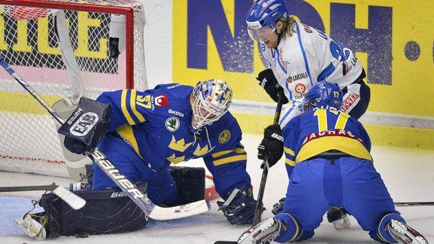 Fin Miika Laht bojuje o puk před brankou švédského gólmana Gustafa Wesslaua.