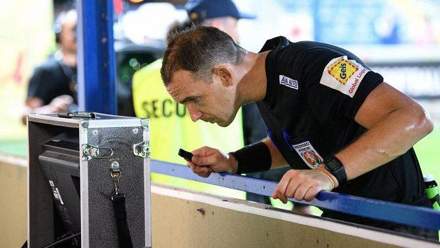 Rozhodčí Pavel Julínek sleduje videozáznam během utkání Liberce se Spartou.