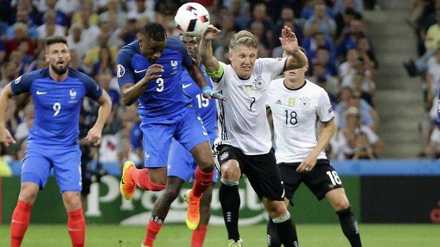 Německý záložník Bastian Schweinsteiger (č. 7)¨hraje rukou v pokutovém území a sudí Rizzoli za to nařizuje pokutový kop pro Francouze.