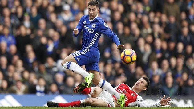 Belgickou hvězdu Chelsea Edena Hazarda se skluzem snaží zastavit Laurent Koscielny z Arsenalu.