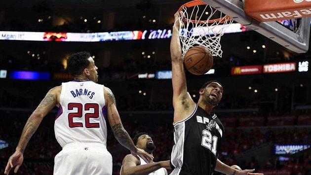 Tim Duncan ze San Antonia dává koš, přihlíží Matt Barnes z Los Angeles Clippers.