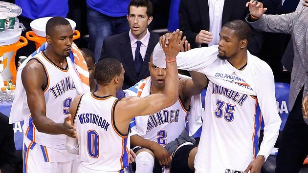 Basketbalisté Oklahomy Kevin Durant (vpravo) a Russell Westbrook (uprostřed) si plácají během zápasu se San Antoniem.