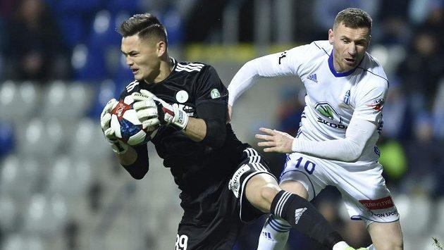 Brankář Bohemians Patrik Le Giang chytá míč před Murisem Mešanovičem z Mladé Boleslavi.