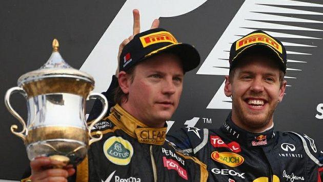 """Sebastian Vettel dělá na stupních vítězů """"oslí uši"""" Kimi Räikkönenovi."""