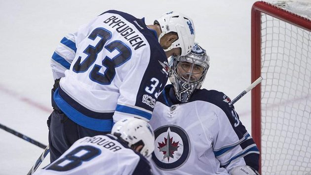 Český brankář Ondřej Pavelec a obránce Dustin Byfuglien oslavují výhru Winnipegu na ledě Dallasu.