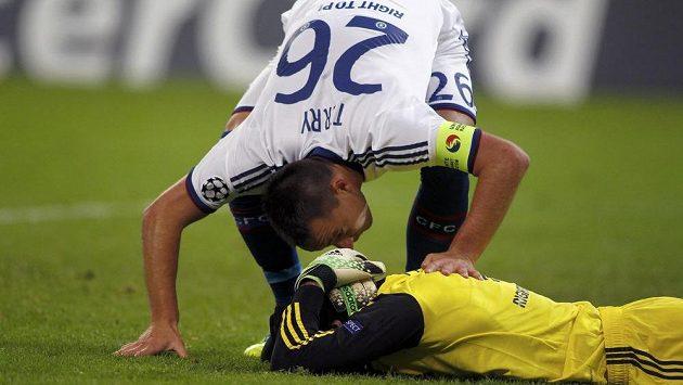 Stoper Chelsea John Terry (s číslem 26) se sklání nad Petrem Čechem poté, co se brankář londýnského týmu udeřil v utkání v Bukurešti hlavou o tyč.