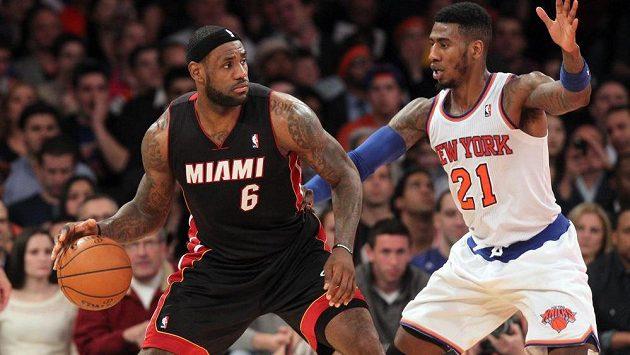 Hvězda Miami LeBron James (6) s míčem vedle bránícího Imana Shumperata (21) z New York Knicks.