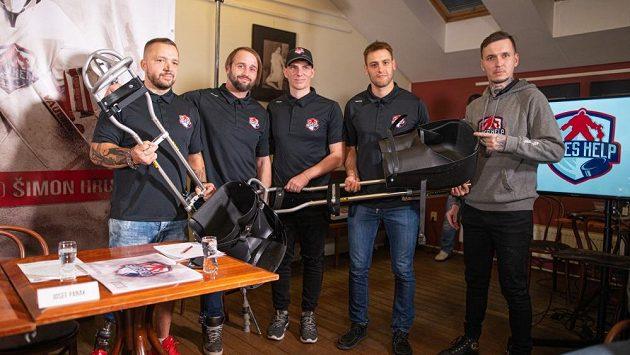 Extraligoví brankáři Jan Lukáš (úplně vpravo) a Daniel Dolejš (druhý zprava) předávají parahokejistům nové saně.