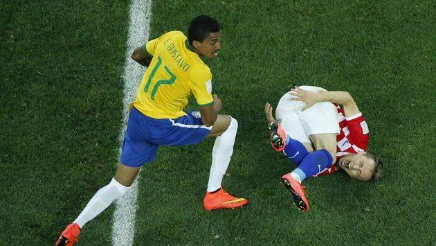 Luka Modrič (vpravo) z Chorvatska v nefotbalové pozici po nevybíravém zákroku Brazilce Luize Gustava v otevíracím zápase světového šampionátu.