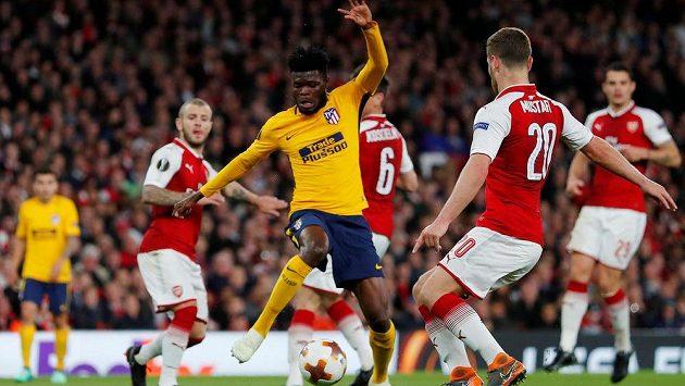 Thomas Partey z Atlétika Madrid se snaží v semifinále Evropské ligy obelstít Shkodrana Mustafiho z Arsenalu.