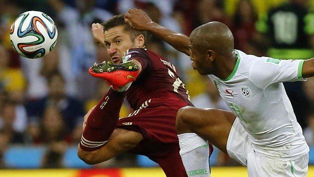 Rus Alexej Kozlov (vlevo) odkopává míč před Jasínem Brahímím z Alžírska.
