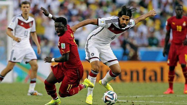 Ghaňan Sulley Muntari (vlevo) v souboji s německým záložníkem Samim Khedirou během zápasu skupiny G na světovém šampionátu v Brazílii.