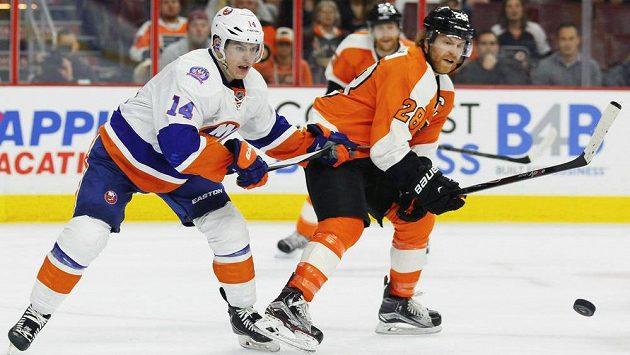 Thomas Hickey (vlevo) z New York Islanders v souboji o puk s Claudem Girouxem z Philadelphie.