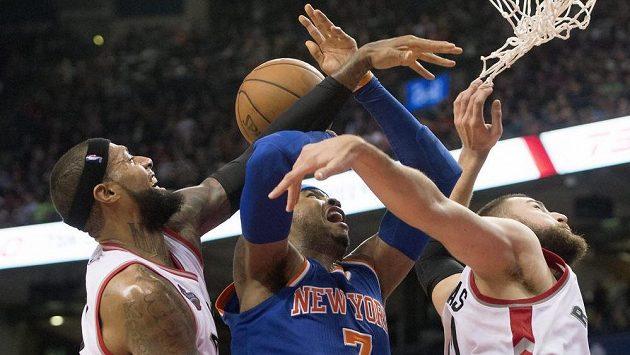 Basketbalista New Yorku Knicks Carmelo Anthony (č. 7) se snaží prosadit přes Jamese Johnsona (vlevo) a Jonase Valanciunase z Toronta.