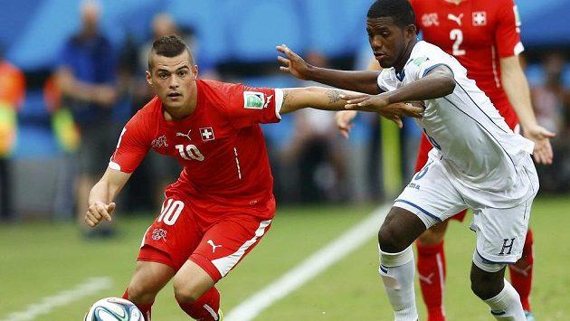 Švýcar Granit Xhaka (vlevo) se zkouší prosmýknout kolem bránícího Juana Carlose Garcíu z Hondurasu.