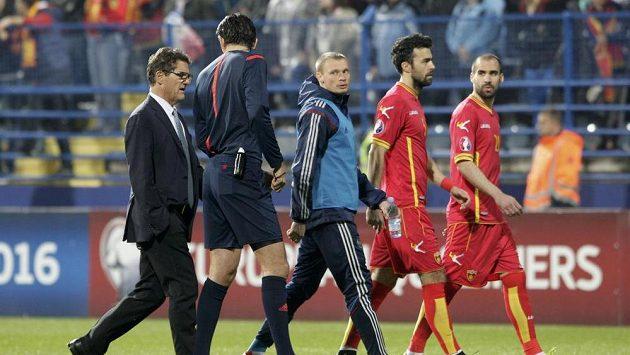 Německý sudí Deniz Aytekin (druhý zleva) hovoří s koučem Ruska Fabiem Capellem (vlevo) při cestě ze hřiště po zranění brankáře Igora Akinfejeva v první minutě.