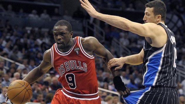 Basketbalista Chicaga Luol Deng (vlevo) přechází přes Turkogla z Orlanda
