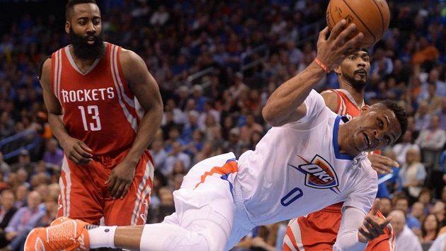 Russell Westbrook z Oklahomy zkouší ohrozit koš Houstonu i v akrobatické pozici, v pozadí James Harden (č. 13).