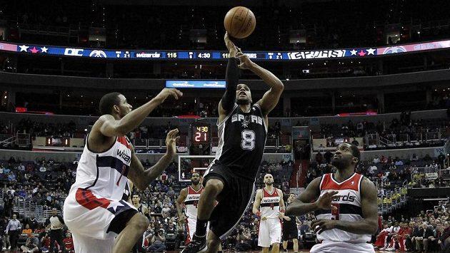 Basketbalista San Antonia Spurs Patty Mills (8) se prodírá mezi bránícími hráči Washingtonu Wizards Trevorem Arizou (vlevo) a Martellem Websterem.