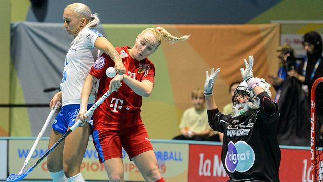 Česká florbalistka Martina Řepková (v červeném) v tvrdém souboji před finskou brankou.