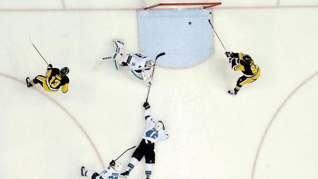 Obránce San Jose Roman Polák (uprostřed) se natahuje a marně se snaží zabránit ve skŕování Philu Kesselovi z Pittsburghu, který otevřel skóre druhého finále Stanley Cupu.