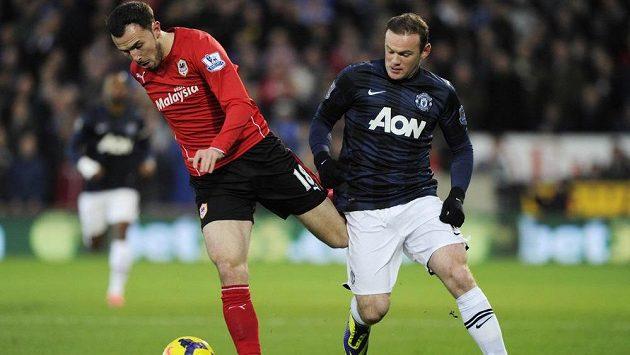 Útočník Manchesteru United Wayne Rooney (vpravo) těsně předtím, než zezadu nakopl svého protivníka Jordona Mutche z Cardiffu.