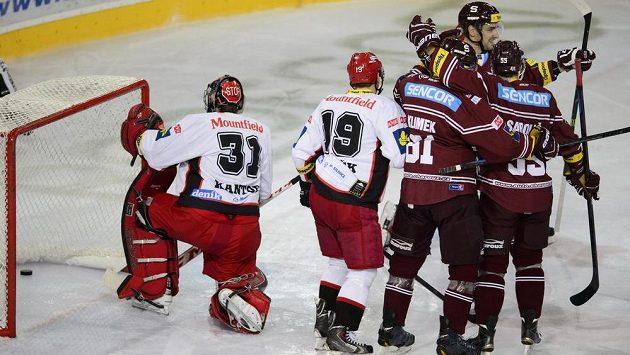 Sparťanští hokejisté se radují ze vstřelení gólu proti Hradci Králové. Vlevo zklamaný brankář Východočechů Pavel Kantor a obránce Martin Pláněk.