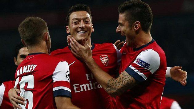 Mesut Özil (uprostřed), autor úvodní trefy Arsenalu v duelu Ligy mistrů s Neapolí, oslavuje gól se spoluhráči Aaronem Ramseym a Olivierem Giroudem.