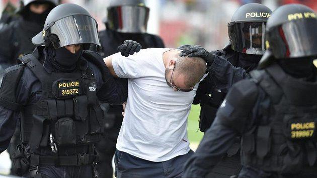 Policisté odvádějí zadržené fanoušky.