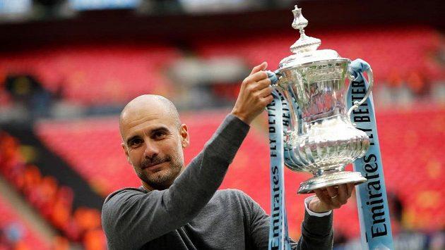 Španělský kouč Josep Guardiola pózuje s trofejí pro vítěze FA Cupu.