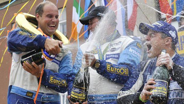Václav Pech (vlevo) a Petr Uhel slaví na náměstí Míru ve Zlíně vítězství v Barum rallye i v celé sérii mistrovství ČR. Vpravo je třetí Tomáš Kostka.